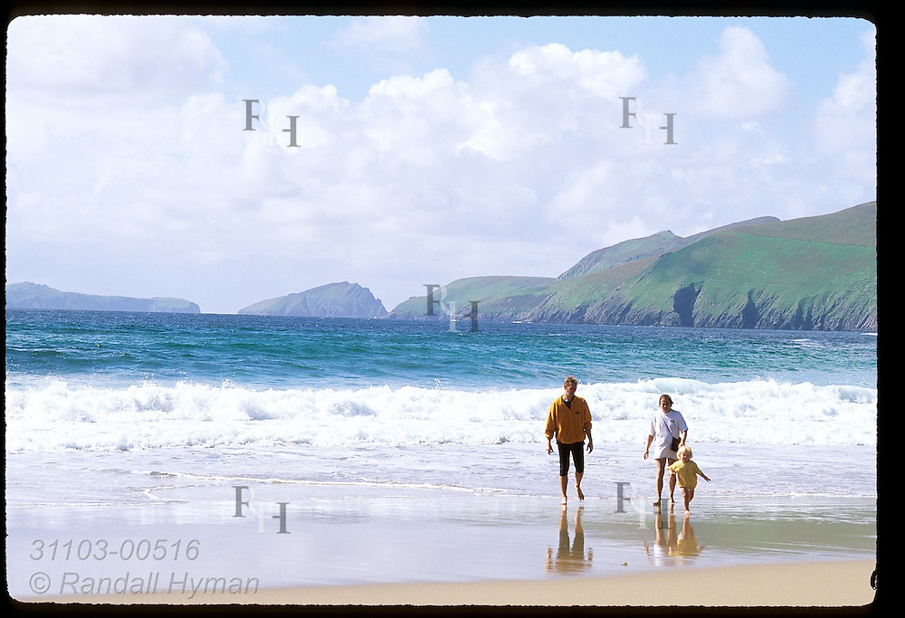 Parents & daughter wet toes in chilly North Atlantic surf of Coumeenole Beach; Dunmore Head & Blasket Islands afar; Dingle, Ireland.