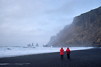 Tourists at Víkurfjara, black sand beach at Vík, South Iceland.