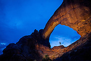A person stands dwarfed below the massive Window Arch in the early morning in Arches National Park.