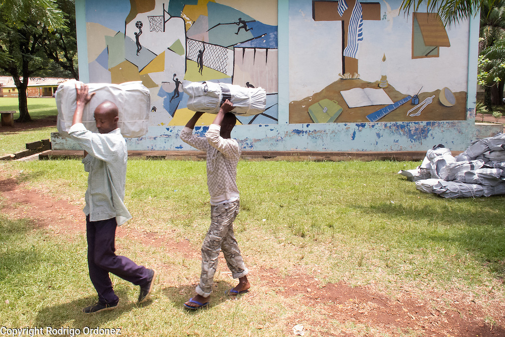 Temporary workers hired by Save the Children walk past a school's wall painting as they unload a truck with relief items in Man, western C&ocirc;te d'Ivoire. <br /> Save the Children chartered a cargo plane carrying urgently needed items, including plastic sheeting, mosquito nets, buckets and water purification tablets. The children's charity will be handing out these basic supplies to 5,000 families displaced by conflict in western C&ocirc;te d'Ivoire to help prevent the spread of diseases.