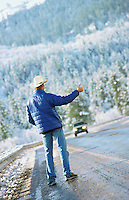Male hitchhiker wearing cowboy hat on mountain roadside
