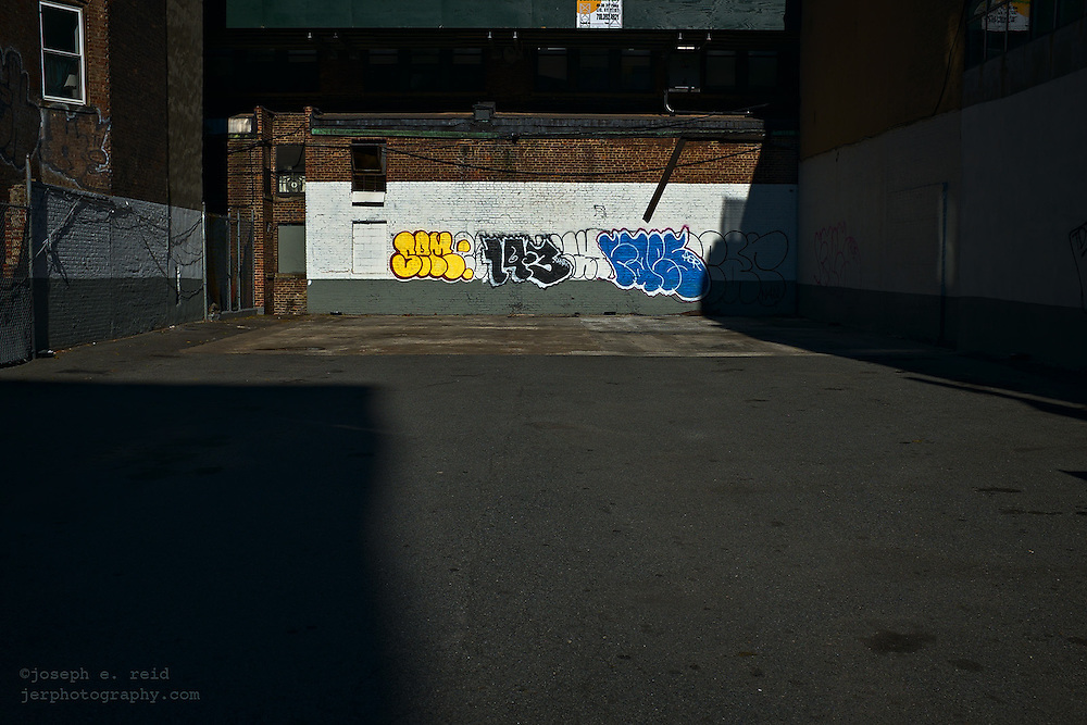 Graffiti on wall in empty parking lot, New York, NY, US