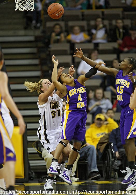 December 22 2010: Iowa guard/forward Hannah Draxten (31), Northern Iowa guard K.K. Armstrong (4), and Northern Iowa guard Mercedees Morgan (45) battle for a rebound during the first half of an NCAA college basketball game at Carver-Hawkeye Arena in Iowa City, Iowa on December 22, 2010. Iowa defeated Northern Iowa 75-64.