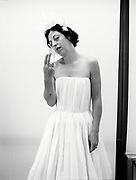 Isabella Blow wearing a white dress holding two fingers up.