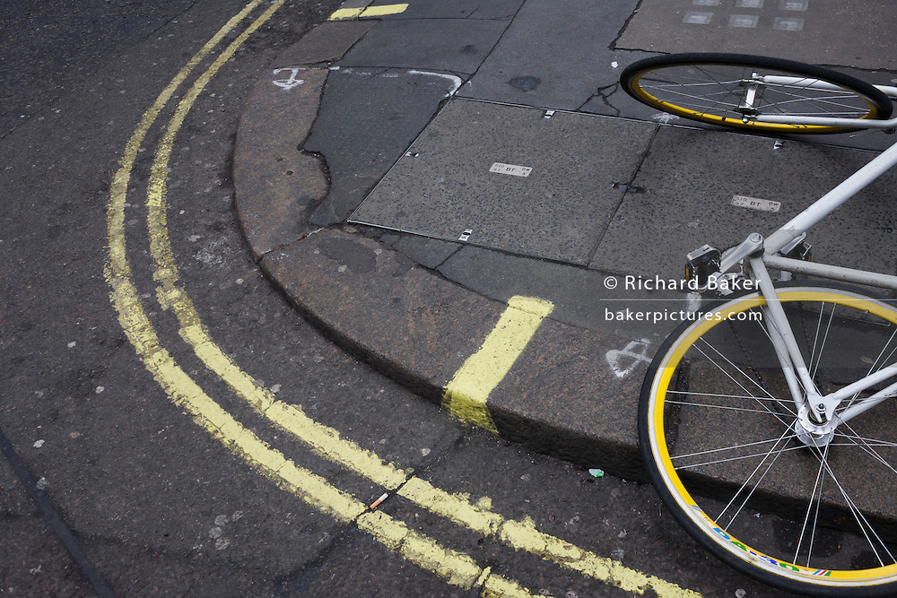 A theme of yellows with double-yellow lines and the yellow wheel rims of a fallen bicycle lying in a city pavement.