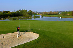 NORMANDY, FRANCE - MAY-01-2007 - Omaha Beach Golf Club Pro Nicolas Poillot chips out of the bunker on the 8th hole of the L'Etang course...Course:  L' Etang (The Lake) Hole 8 - 391 yards - Par 4 (Photo © Jock Fistick)
