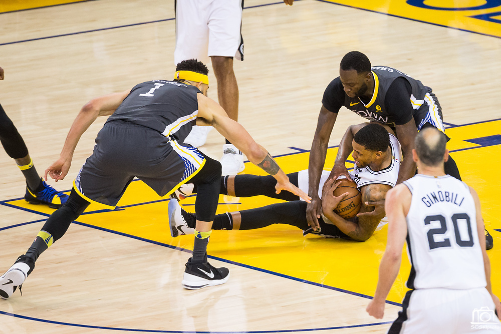 Golden State Warriors forward Draymond Green (23) dives on San Antonio Spurs forward LaMarcus Aldridge (12) for a loose ball during Game 2 of the Western Conference Quarterfinals at Oracle Arena in Oakland, Calif., on April 16, 2018. (Stan Olszewski/Special to S.F. Examiner)