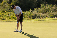 Teenage boy putts in the late afternoon sun at Nicklaus North in Whistler, BC Canada.