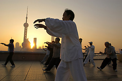 People practicing Tai Chi on The Bund at dawn in Shanghai China