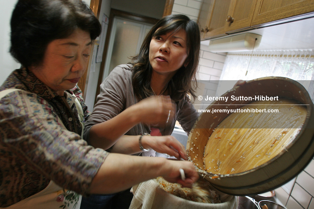 Hiroko Takahashi (on left), cooking in her home with her daughter Masumi Soda, in Hachioji,  Tokyo, Japan, 11.05.2006.