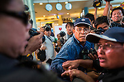 "01 JUNE 2014 - BANGKOK, THAILAND:  A Thai man who protested against the military coup is chased by police in Terminal 21 shopping mall in Bangkok. The Thai army seized power in a coup that unseated a democratically elected government on May 22. Since then there have been sporadic protests against the coup. The protests Sunday were the largest in several days and seemed to be spontaneous ""flash mobs"" that appeared at shopping centers in Bangkok and then broke up when soldiers arrived. Protest against the coup is illegal and the junta has threatened to arrest anyone who protests the coup. There was a massive security operation in Bangkok Sunday that shut down several shopping areas to prevent the protests but protestors went to malls that had no military presence.   PHOTO BY JACK KURTZ"
