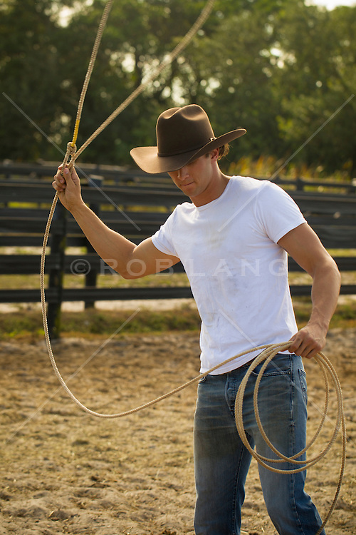 young good looking cowboy wearing a white tee shirt and cowboy hat at a ranch using a lasso