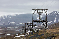 An old wooden tram way used for transporting coal from the hills overlooking Longyearbyen stands out against the barren terrain of Spitsbergen.  Longyearbyen, Svalbard, Norway.