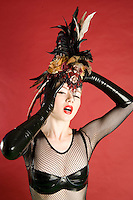 Portrait of pinup woman wearing feather headgear over colored background