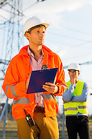 Male architect with clipboard working at site while coworker standing in background