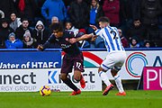 Alex Iwobi of Arsenal (17) takes on Tommy Smith of Huddersfield Town (2) during the Premier League match between Huddersfield Town and Arsenal at the John Smiths Stadium, Huddersfield, England on 9 February 2019.