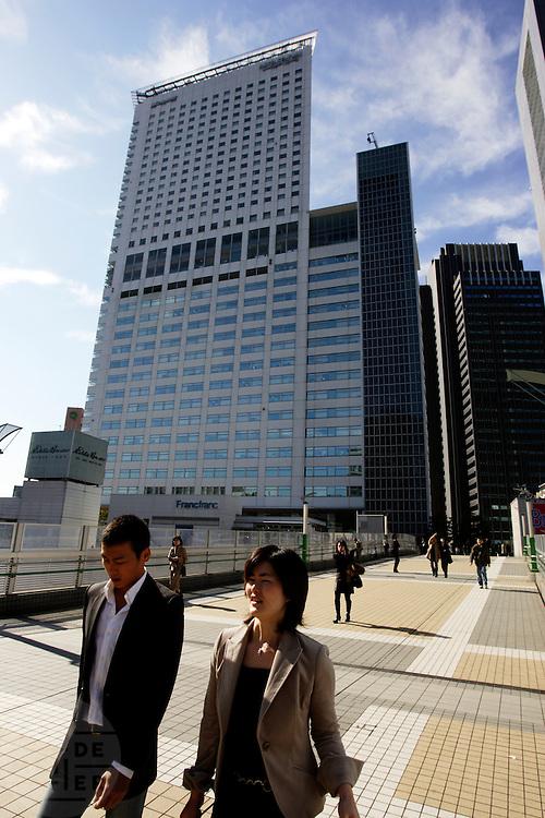 Een man en vrouw lopen over de brug over het spoor in Tokyo, richting een groot winkelcentrum. Op de achtergrond staat een groot hotel, met de lobby op de 20e etage. De bovenste drie verdiepingen zijn eigendom van Microsoft