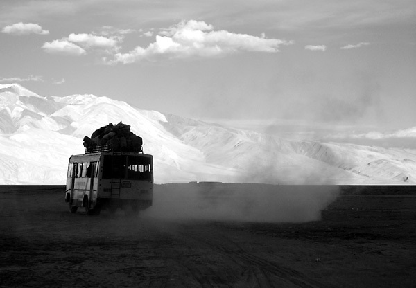 Tso Moriri - Luglio 2009: un pullman corre su una strada polverosa su un altopiano a 4000mt di altitudine. <br /> <br /> Tso Moriri - July 2009: a public bus passes by on a dusty plateau at a altitude of 15000ft asl.