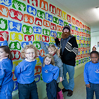 Artisit David O'Rourke ,Ennis with some of the pupils from Holy Family junior school ,Ennis who worked on the hand print Mural as part of the Artists in schools program. Photograph by Eamon Ward