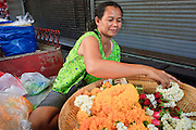 Mar. 8, 2009 -- BANGKOK, THAILAND:  A woman makes and sells flower garlands at a Buddhist shrine in the Chatuchak Weekend Market. The market covers an area of 35 acres with more than 15,000 shops and stalls. It has over 200,000 visitors each day it's open (Friday - Sunday), and they spend an estimated total of 30 million baht (approx US$750,000). The range of products on sale is extensive, and includes household accessories, handicrafts, religious artifacts, art, antiques, live animals (which unfortunately are frequently caged in cruel conditions), books, music, clothes, food, plants and flowers. Photo by Jack Kurtz / ZUMA Press