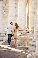 Couple walking between pillars Rome Italy back view