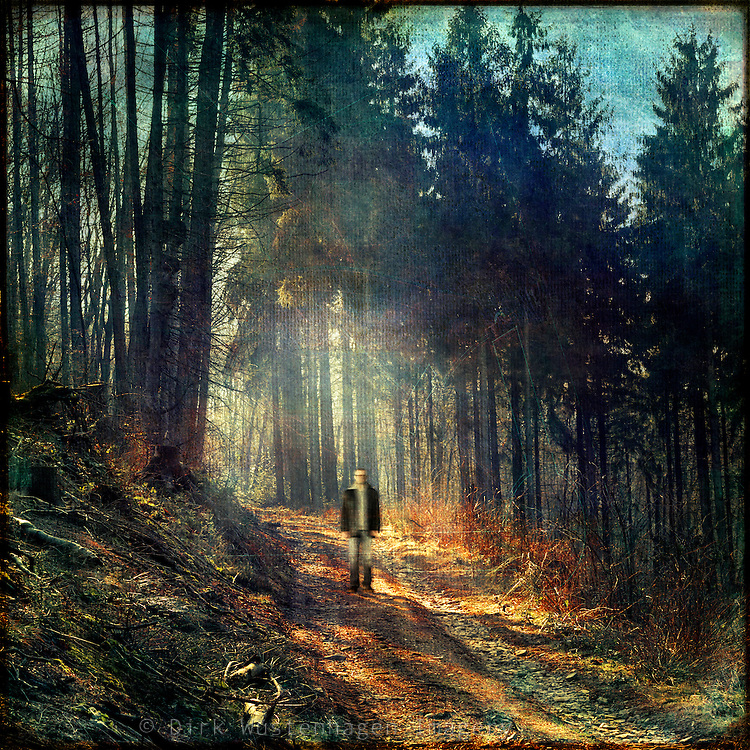 silhouette of a man in a light drenched forest scene - manipulated and texturized photograph