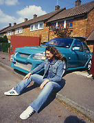 A girl sat on the pavement next to a customised car, UK, 2000's