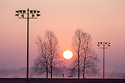 Silhouette of jogger crossing dam at Lake Fayetteville in Fayetteville, Arkansas.