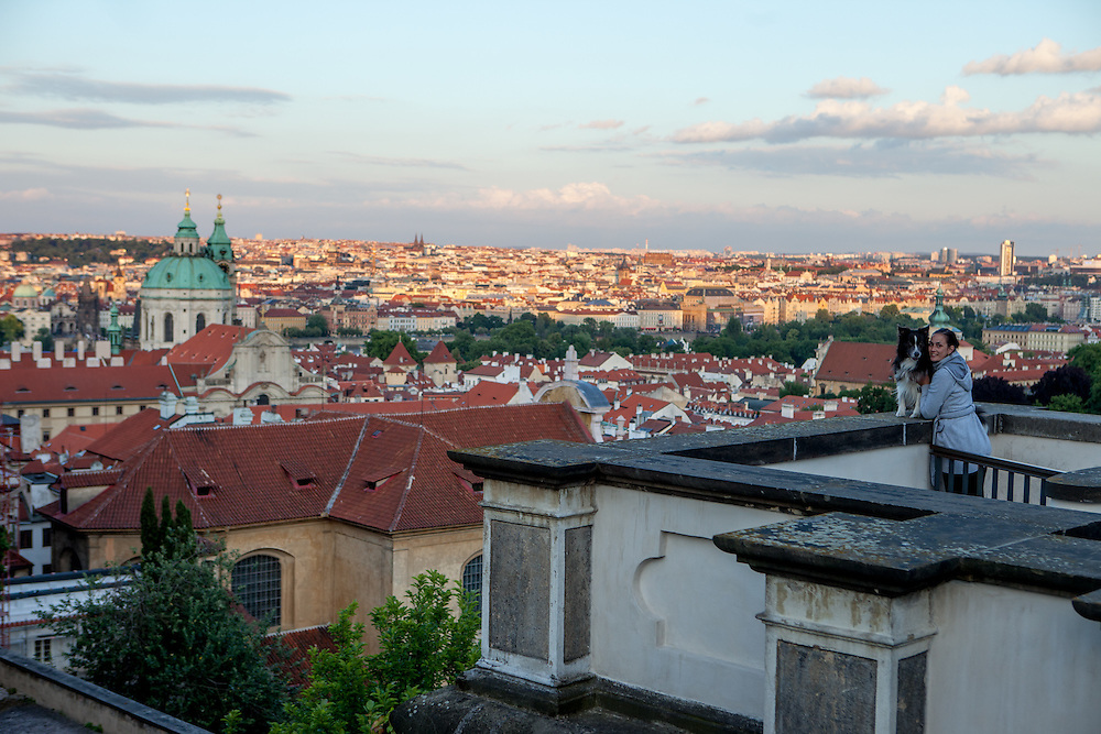 A woman with her dog above the Prague cityscape close to Prague Castle Square.