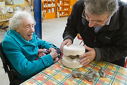 Visually impaired people with carers on outing to Denby Pottery. Helper with elderly lady pressing clay into plaster mould.