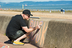 A mile of buskers on Portobello Prom this afternoon in the nonth annual Big Beach Busk. The day starts with the man who first came up with the idea for the busk, ?Paul Lambie and his team of local helpers chalking out the circular 'pittches' all along the Prom. And then the buskers arrive - all ages, all styles of music, from solo performers to big bands. The place is heaving! Paul Lambie chalking out the performance spaces.<br /> <br /> <br /> © Jon Davey/ EEm