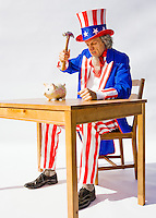 Uncle Sam sitting at a table about to break his piggy bank with a hammer...Model Release: 20080813_MR_A
