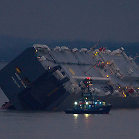 Airsea rescue helicopetr and life boats are in attendence, Car Carrier Hoegh Osaka, from Singapore, goes aground on the Brambles Sand Bank  in the Solent. Hampshire, England, UK, . 4 January 2015. Photograph by © Patrick Eden/Alamy .