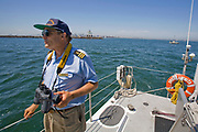 """Captain Charlie Moore, Maiden voyage of the """"Junk"""" raft, out of Long Beach Harbor. 5/18/08.  in June of 2008, the raft named """"Junk""""  will sail 2,100 miles from Los Angeles to Hawaii to bring attention to the plastic marine debris (nicknamed the plastic soup) accumulating in the North Pacific Gyre. Designed by Dr. Marcus Eriksen and Joel Paschal, the raft is constructed from 20,000 plastic bottles, an airplane fuselage, discarded fishing nets, a solar generator, and a bicycle generator. California, USA"""