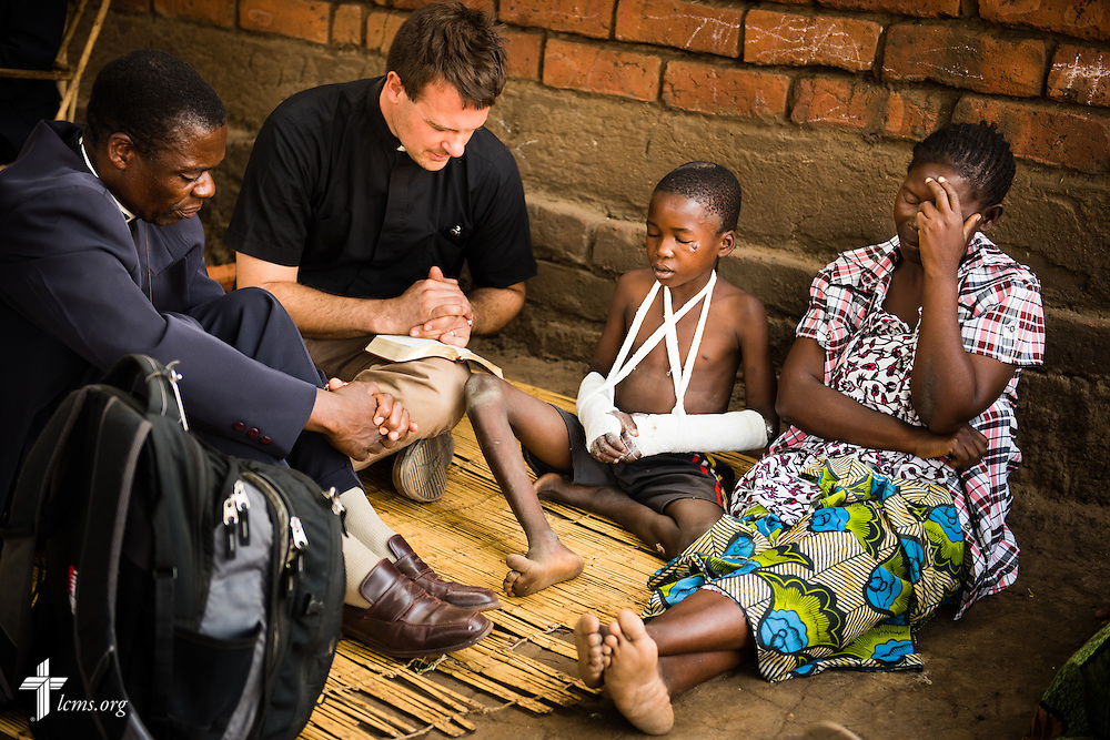 The Rev. Shauen Trump, LCMS missionary and area director for Eastern and Southern Africa, prays with an injured boy and his mother following worship on Sunday, Sept. 27, 2015, in Chingale, Malawi. He is joined by the Rev. Davis Wowa, executive chairman of the Confessional Lutheran Church–Malawi Synod. LCMS Communications/Erik M. Lunsford