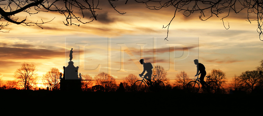 © Licensed to London News Pictures. 28/12/2015. London, UK.  Cyclists pass the Diana Fountain at sunrise in Bushy Park. Photo credit: Peter Macdiarmid/LNP