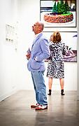 Man in seersucker jacket views art work at Art Basel Miami Beach