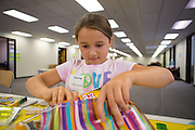 Brynne (10) volunteers with her mother, Shannon Hernandez, Symantec of Cupertino, at the Family Giving Tree in Milpitas, Calif., on Aug. 3, 2012.  Over 15,000 donated backpacks and school supplies will be processed during the Family Giving Tree's Back to School Drive.  Photo by Stan Olszewski/SOSKIphoto.
