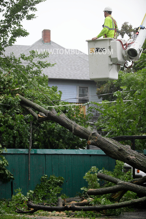 Middletown, NY - A Nelson Tree Service employee in a bucket truck looks at a tree that fell across a road and onto wires during a thunderstorm on Aug. 22, 2009. Winds from the storm knocked down many trees in the area.