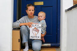 © Licensed to London News Pictures. 03/06/2020. London, UK. Natasha and her 1 year old son Rudi, in Haringey, north London take part in the 'Take The Knee' protest on their doorstep. The protest has been organised by anti-racism campaign group, Standup to Racism, following the death of George Floyd in Minneapolis, USA. The 46-year-old African American died last week after a police officer held him down by pressing a knee into his neck. Photo credit: Dinendra Haria/LNP
