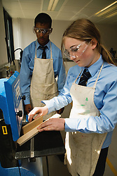 Secondary school student cutting machine to shape wood in a Design technology lesson,