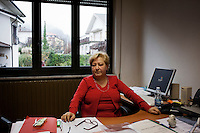 Sesta Godano, Italy - 14 January, 2013: Principal of elementary school Cinzia Cacone sits at her desk in her office  in Sesta Godano, Italy, on 14 January, 2013. <br /> <br /> Sesta Godano is a town in the province of La Spezia, in the Liguria region, with a population of about 1,400.  Because of a low number of children in the area, students in the elementary and seconday have been grouped in multigrade classes. According to the ISTAT (Italian National Statistical Institute) Liguria is the oldest of the Italian regions, with the highes ageing index of 232 percent compared to the national average of 144,5 percent and the EU average of 111,3 percent (data is from 2010). In Liguria there are almost twie as much deaths than births. The average age in Liguria is 48 years old. <br /> <br /> Italy is ageing. According to ISTAT, the average age will rise from 43.5 in 2011 to a maximum of 49.8 in 2059.