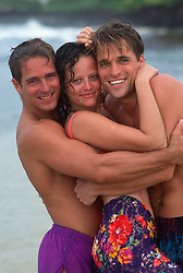 Two men and a woman hugging and smiling on the beach