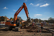 Builders use an orange JCB to lay drainage pipes in the ground around the foundations of a new build housing construction site in Norwich, Norfolk.  United Kingdom (photo by Andrew Aitchison / In pictures via Getty Images)