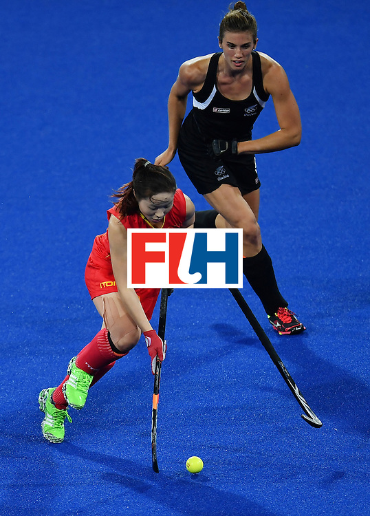 New Zealand's Brooke Neal drops her stick as she vies with China's Peng Yang during the women's field hockey China vs New Zealand match of the Rio 2016 Olympics Games at the Olympic Hockey Centre in Rio de Janeiro on August, 13 2016. / AFP / MANAN VATSYAYANA        (Photo credit should read MANAN VATSYAYANA/AFP/Getty Images)
