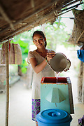 Bisnu replenishes the biosand water filter outside her family home in Sharanamati Village.