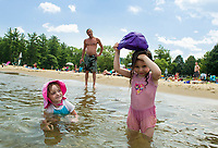 """Lily Lafond watches Layleah Wells pour her cap full of water over her head to cool off with """"Papa"""" Jeff Wells at Weirs Beach on Wednesday afternoon.  (Karen Bobotas/for the Laconia Daily Sun)"""