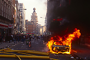 A Porsche car burns fiercely outside the theatre where Will Russel's Blood Brothers is showing, during the Poll Tax riot in the UK capital, on 31st March 1990, in St. Martin's Lane, London, England. Angry crowds, demonstrating against Margaret Thatcher's local authority tax, stormed the Whitehall area and then London's West End, setting fire to a construction site and cars, looting stores up Charing Cross Road and St Martin's Lane. The anti-poll tax rally in central London erupted into the worst riots seen in the city for a century. Forty-five police officers were among the 113 people injured as well as 20 police horses. 340 people were arrested.