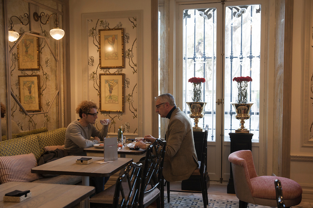 Two men enjoy breakfast at one of the fine cafes at Plaza de oriente, right on front of the Royal Palace, in Madrid, Spain.