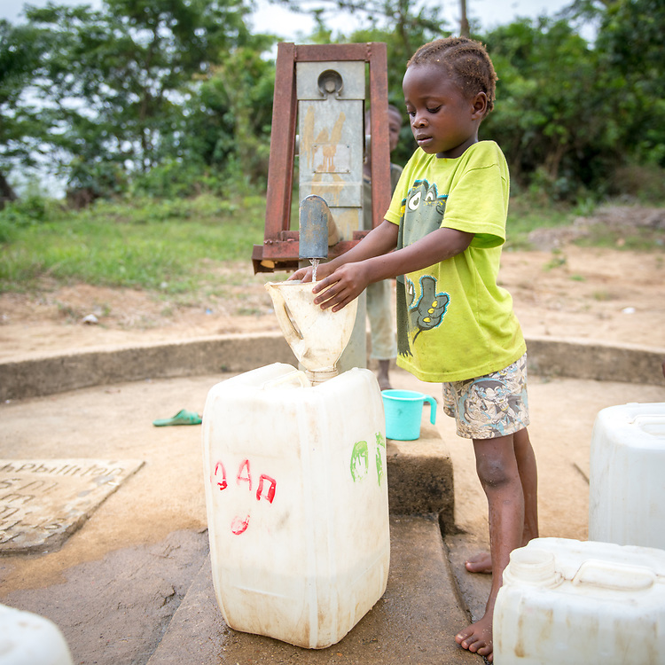 A young girl pumps water in Ganta, Liberia